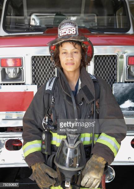 African female firefighter in front of fire truck