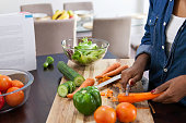 African woman cutting up vegetables and peeling carrots while reading from her cook book, preparing lunch. Cape Town, Western Cape, South Africa.