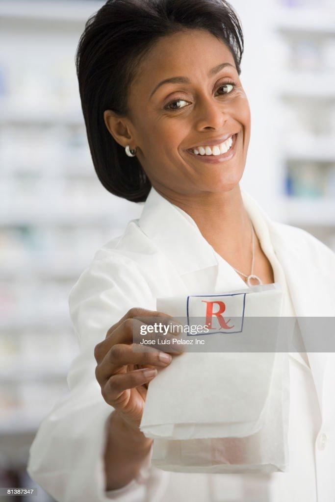 African female pharmacist handing over prescription : Stock Photo