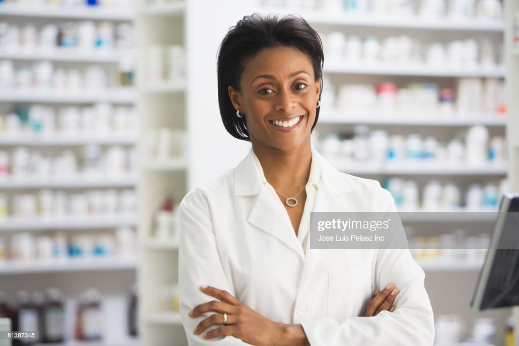 African female pharmacist with arms crossed : Stock Photo