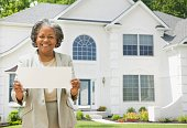 African female real estate agent holding contract to house