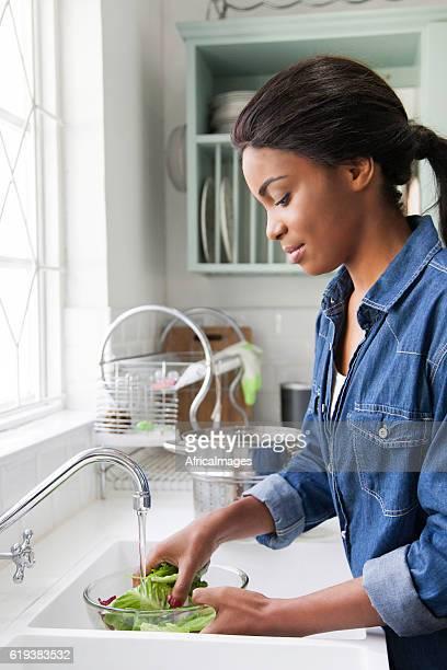 African female rinsing lettuce.