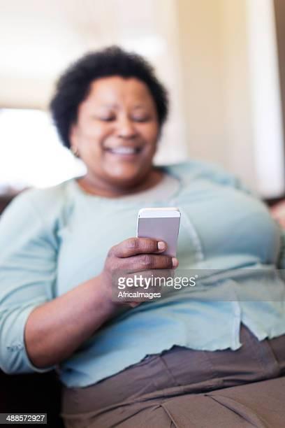 Femme d'Afrique senior lire un SMS sur son mari.