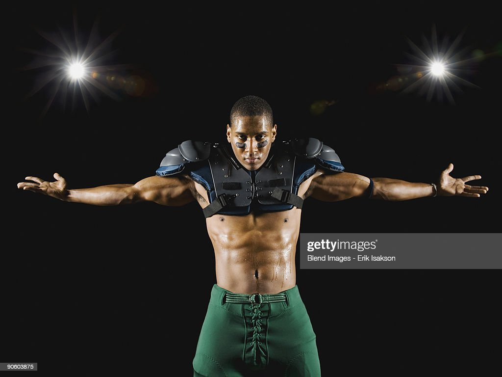 African football player wearing protective pads with arms outstretched