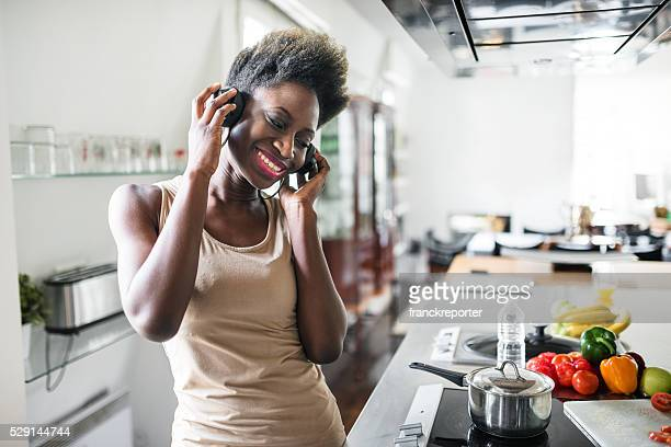 african french woman listening music on the kitchen