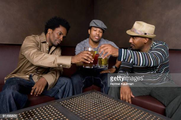 African friends toasting with beer in nightclub