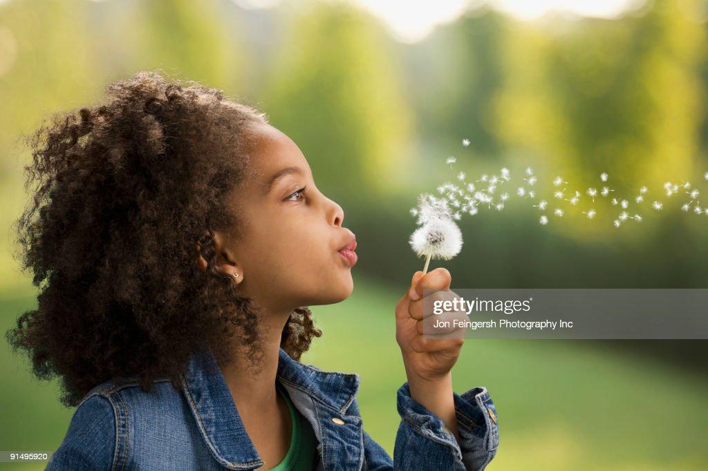 African girl blowing dandelion seeds : Stock Photo