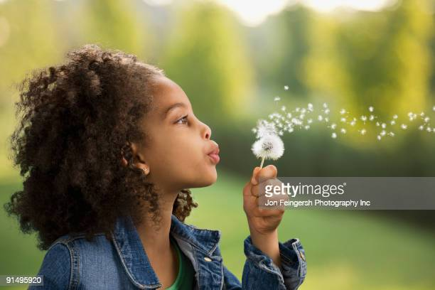 African girl blowing dandelion seeds