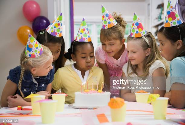 African girl blowing out candles at birthday party