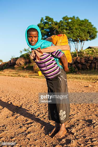 African girl carrying water from the river, Ethiopia, Africa