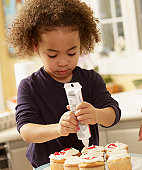African girl decorating cupcakes