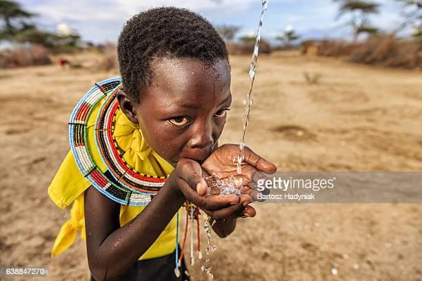 African girl from Samburu tribe drinking fresh water, East Africa