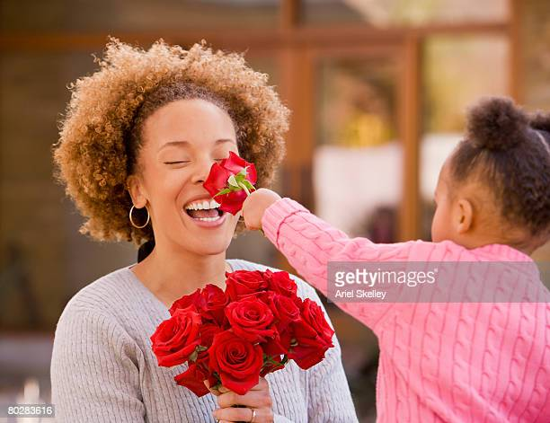 African girl giving flowers to mother