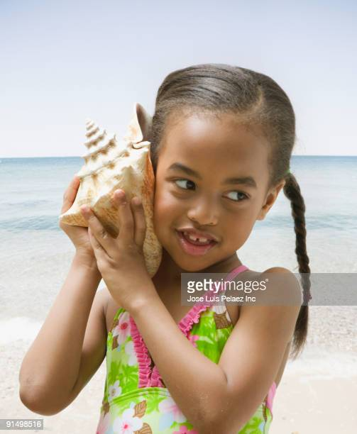 African girl holding conch shell to ear