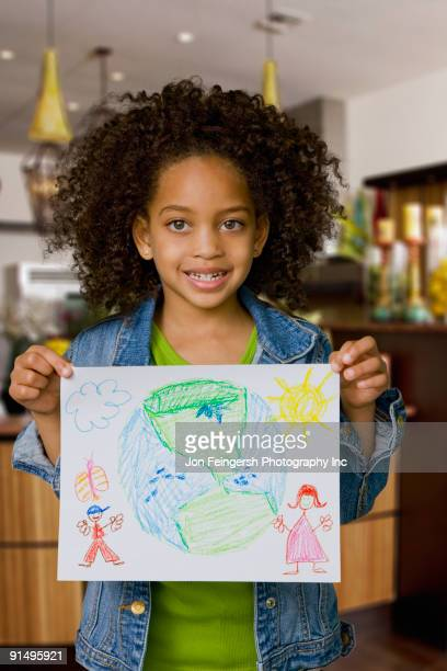 African girl holding drawing of the Earth
