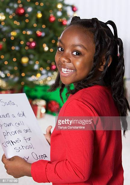 African girl holding letter for Santa Claus