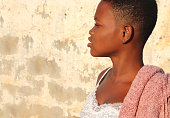 Beautiful African girl stands in front of a white wall.