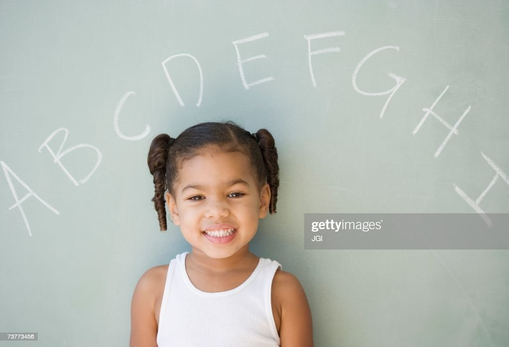 African girl leaning against blackboard : Stock Photo