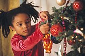 African girl putting ornament on Christmas tree