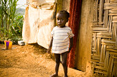African girl standing outside her house