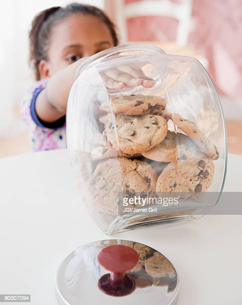 African girl taking cookie from jar