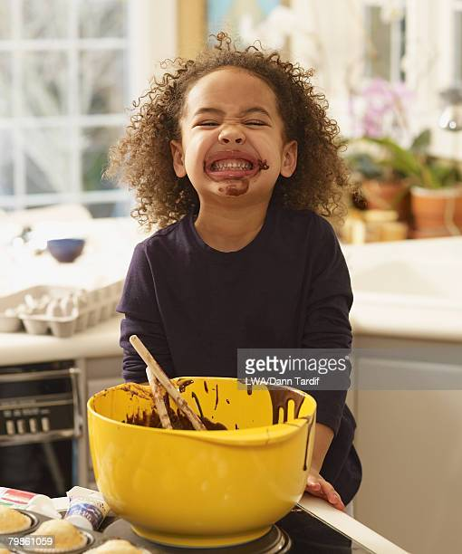 African girl with cupcake batter on face