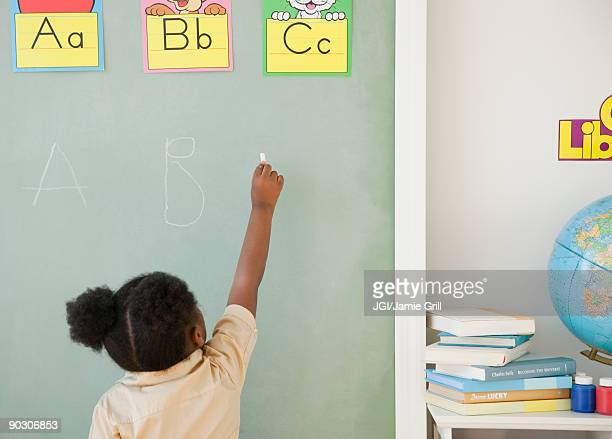 African girl writing on blackboard
