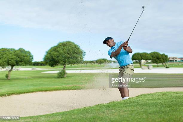African golfer getting his ball out of the bunker.