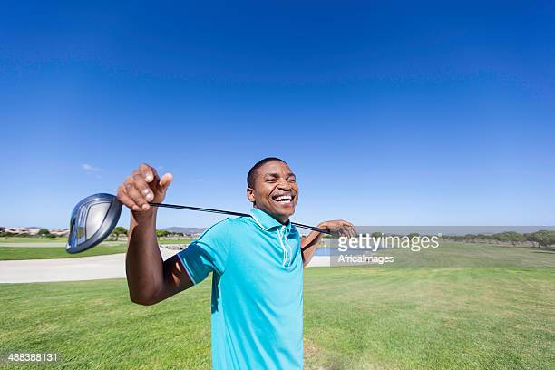 African golfer laughing, holding a golf club over his shoulder.