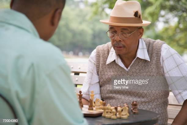 African grandfather and adult son playing chess outdoors