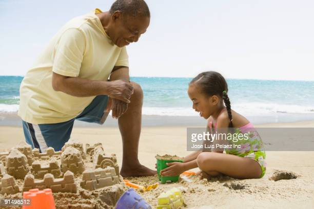 African grandfather and granddaughter building sand castle