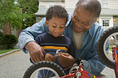 African grandfather and grandson fixing bicycle