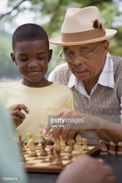 African grandfather and grandson playing chess outdoors