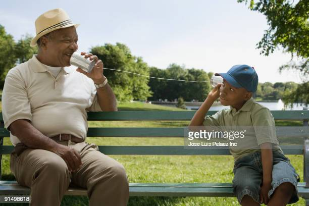 African grandfather and grandson playing with tin can phone