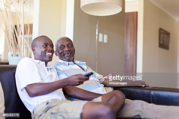 African grandfather and grandson watching television together