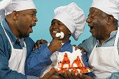 African grandfather, father and son wearing chef's hats with cake