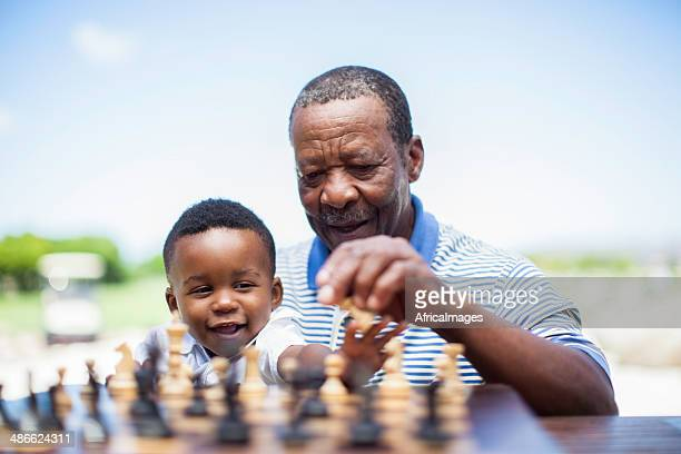 African grandfather playing chess with his grandson