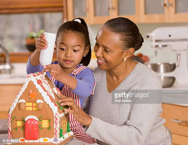 African grandmother and granddaughter decorating gingerbread house