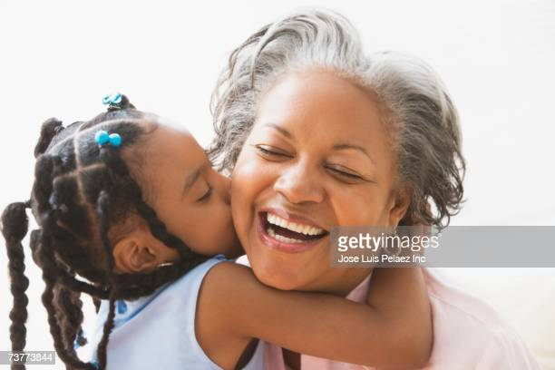 African grandmother and granddaughter hugging