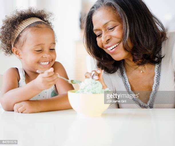 African grandmother and granddaughter sharing ice cream