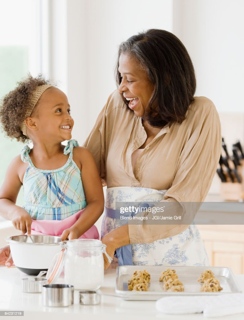 African grandmother baking cookies with granddaughter : Stock Photo