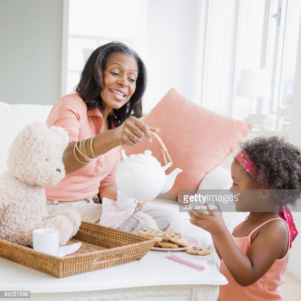 African grandmother having tea party with granddaughter