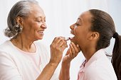 African grandmother helping granddaughter apply lipstick