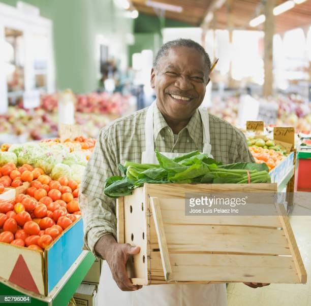 African grocer holding box of lettuce