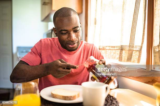 Afrikanische Mann tun Frühstück wie zu Hause fühlen.