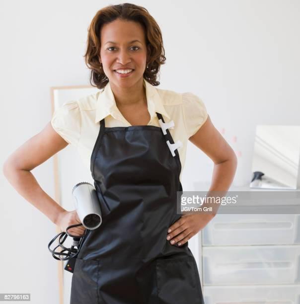 African hairdresser holding hair dryer
