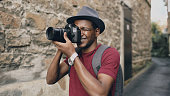 African american happy tourist taking photo on his dslr camera. Young man standing near brick wall of famous building in Europe