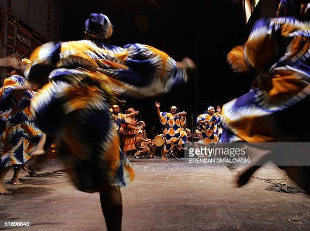 African Heritage Dancers dance to the African Heritage Drummers during a Kwanzaa celebration 26 December 2004 at the Lincoln Theater in Washington...