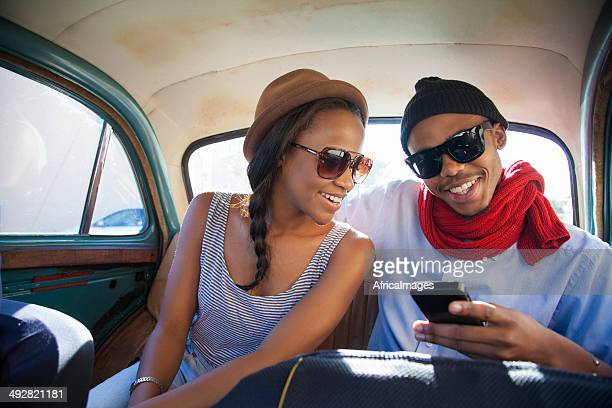 African hipster couple surfing the web on a phone