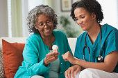 African home nurse reviewing prescription bottle with patient